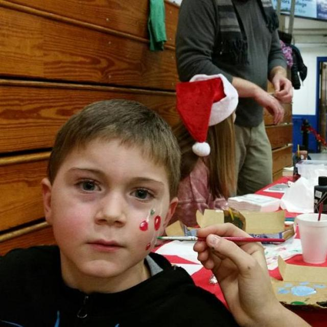 A child having his face painted with Christmas decorations