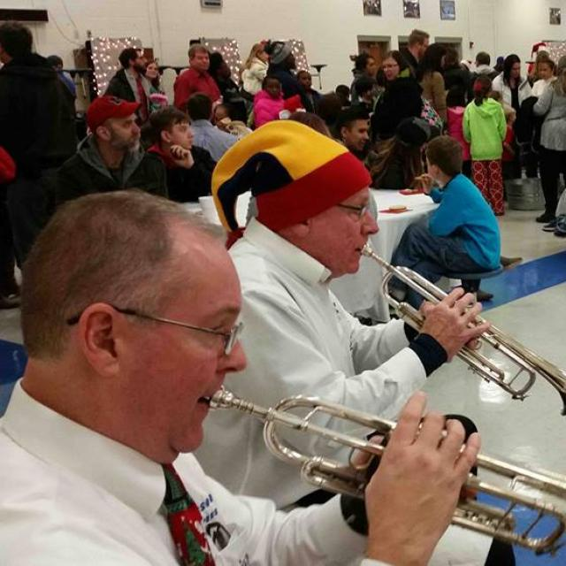 Live christmas music is performed by a brass quintet